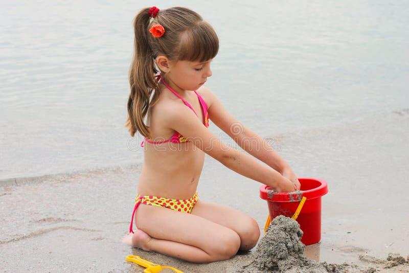 Ragazza che gioca con la sabbia sulla riva di mare immagine stock