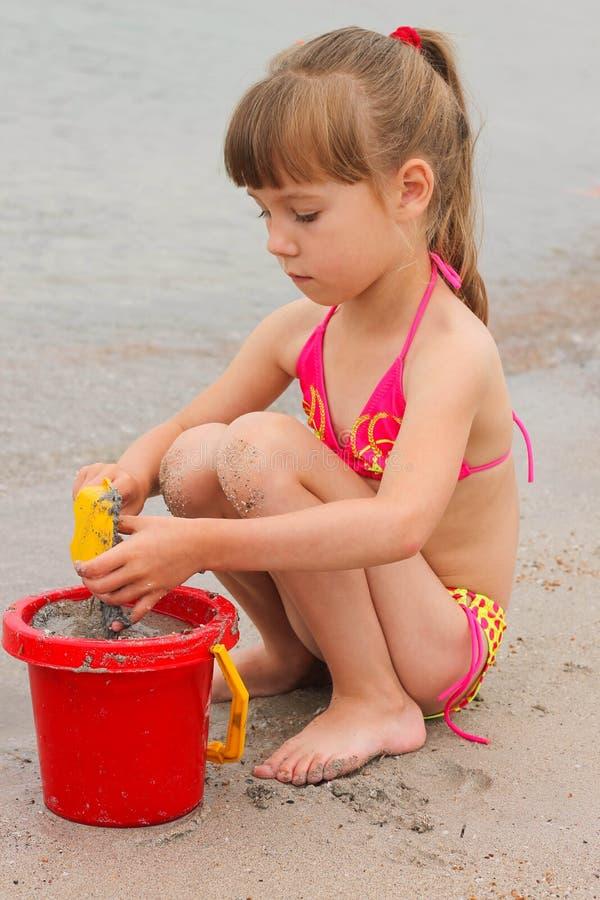 Ragazza che gioca con la sabbia sulla riva di mare fotografie stock libere da diritti
