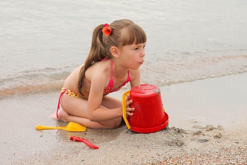 Ragazza che gioca con la sabbia sulla riva di mare fotografie stock