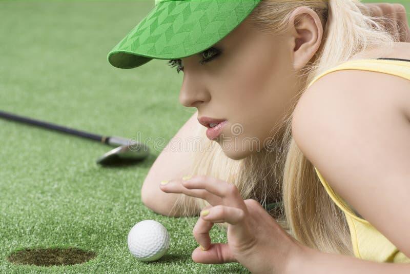 Ragazza che gioca con la sfera di golf, è nel profilo immagine stock