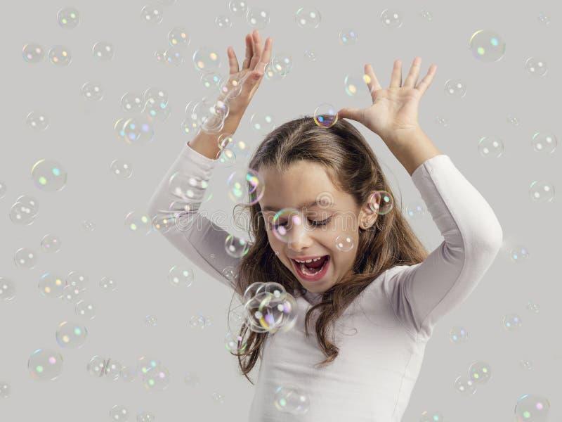 Ragazza che gioca con le bolle di sapone fotografia stock