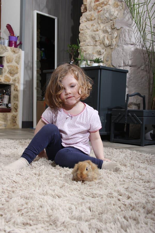 Ragazza che gioca con un coniglietto immagini stock