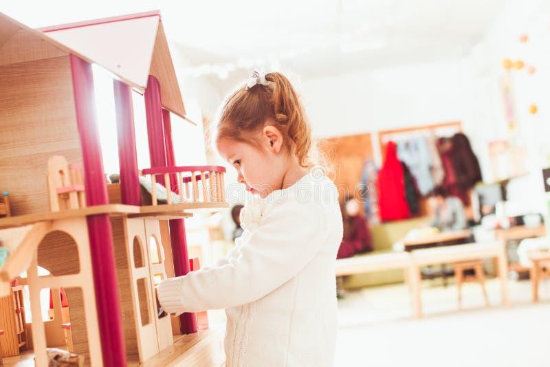 Ragazza che gioca con una casa delle bambole fotografia stock