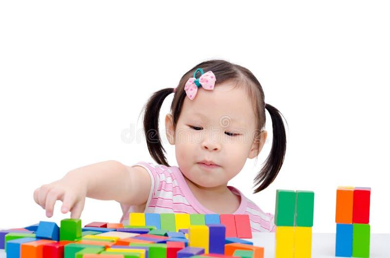 Ragazza che gioca i blocchi di legno variopinti immagini stock