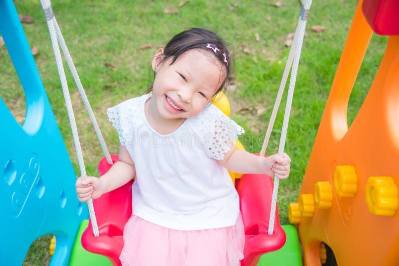 Ragazza che gioca la sedia e sorriso dell'oscillazione in campo da giuoco immagini stock libere da diritti