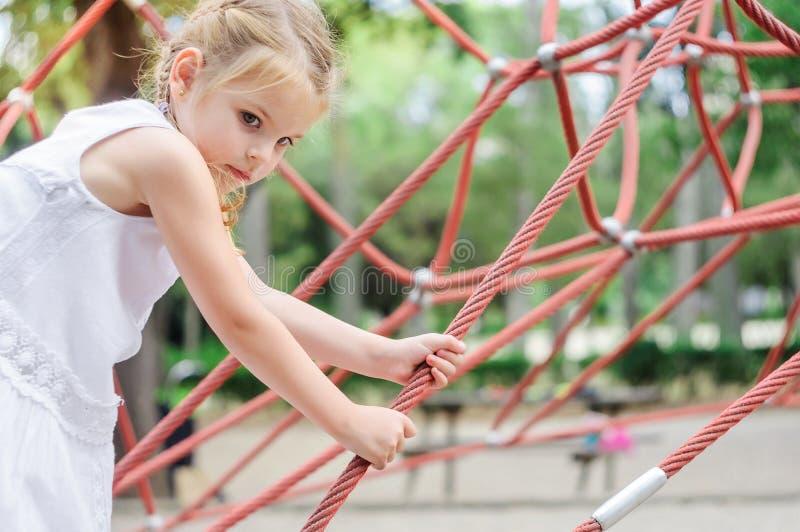 Ragazza che gioca nella sosta Bambina che scala sul playg all'aperto immagini stock libere da diritti