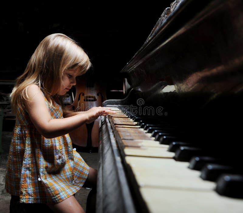 Ragazza che gioca su un piano. immagini stock