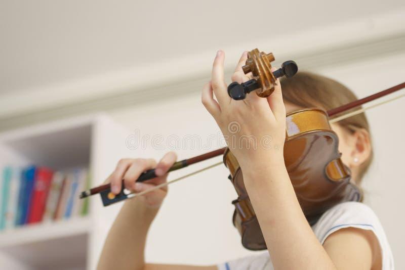 Ragazza che gioca violino nella stanza bianca fotografie stock