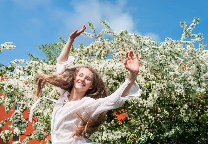 Ragazza che gode degli alberi di fioritura vicini di primavera immagine stock libera da diritti