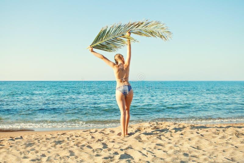 Ragazza che gode del sole, rilassantesi sulla spiaggia del mare e tenente il ramo della palma fotografie stock