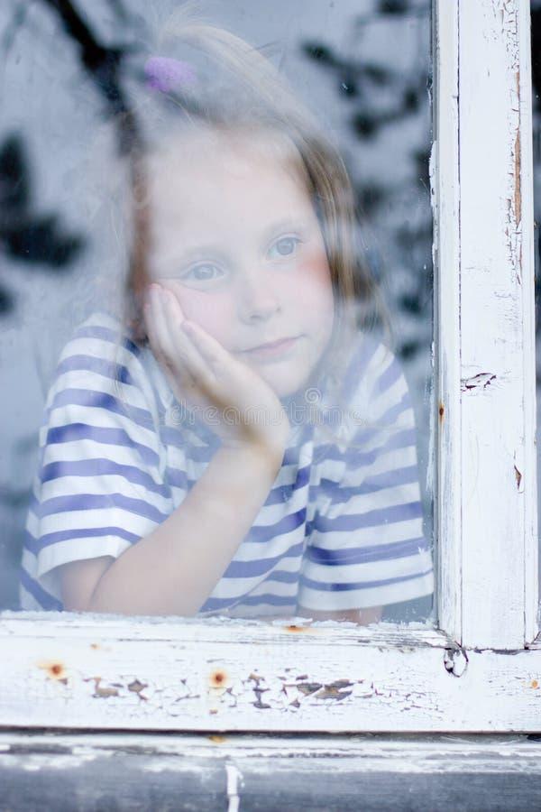 Ragazza che guarda dalla finestra immagini stock libere da diritti