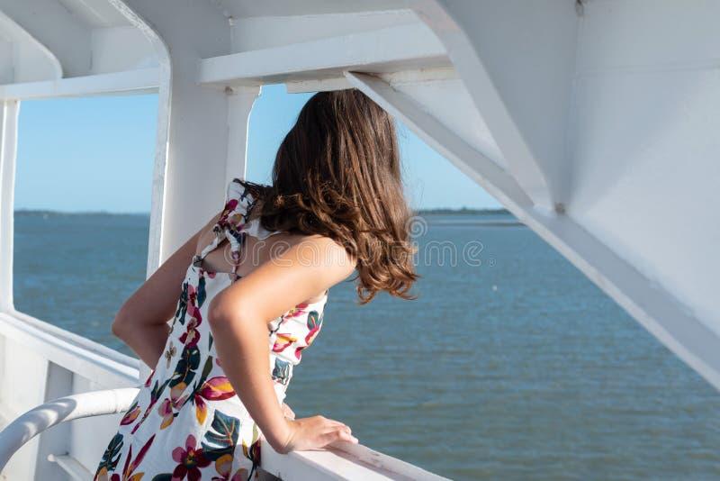 Ragazza che guarda fuori al mare dal traghetto fotografia stock libera da diritti