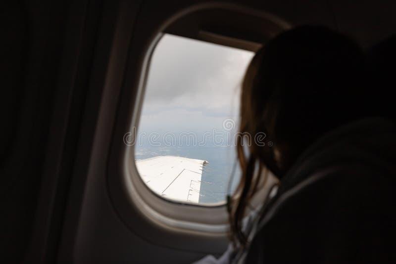 Ragazza che guarda fuori finestra dell'aeroplano in volo fotografie stock libere da diritti