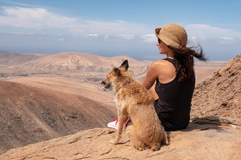 Ragazza che guarda il panorama con il suo cucciolo di cane immagine stock