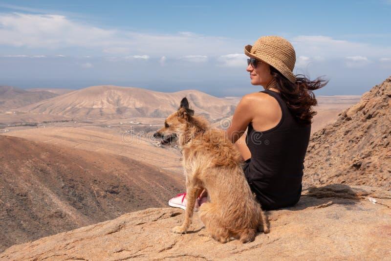 Ragazza che guarda il panorama con il suo cucciolo di cane fotografia stock