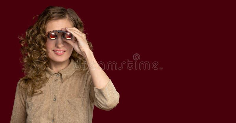 Ragazza che guarda tramite il binocolo al lato immagine stock