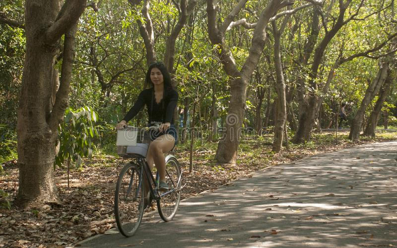 Ragazza che guida una bicicletta nel giardino fotografie stock