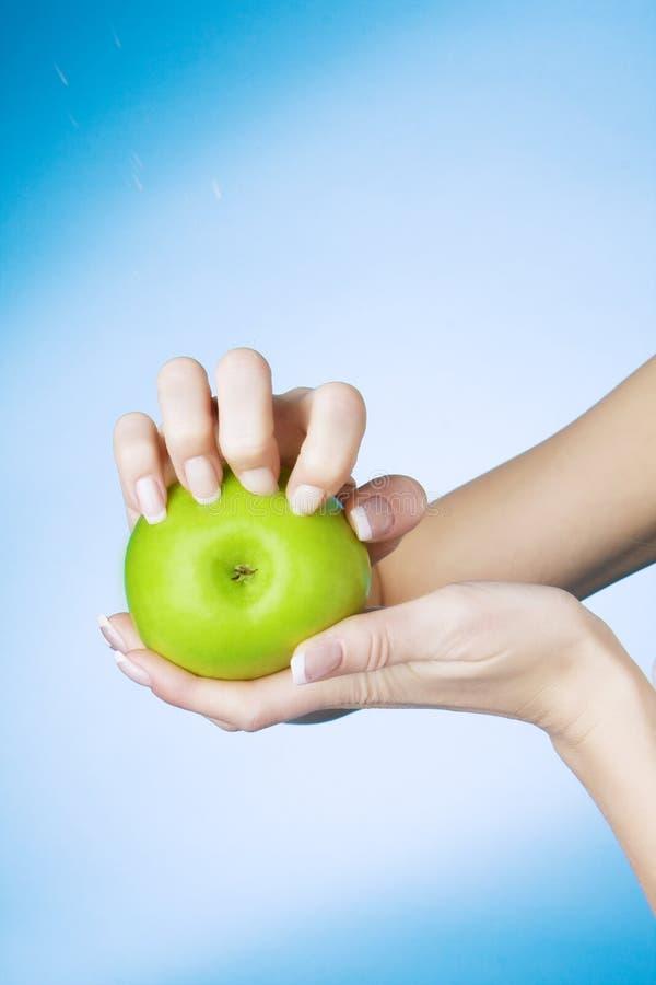 Ragazza che ha grippato i chiodi la mela verde immagine stock libera da diritti