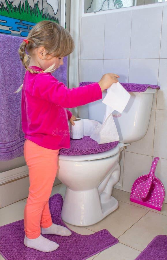 Ragazza che il bambino sta stando alla toilette con la carta igienica in mani fotografia stock libera da diritti