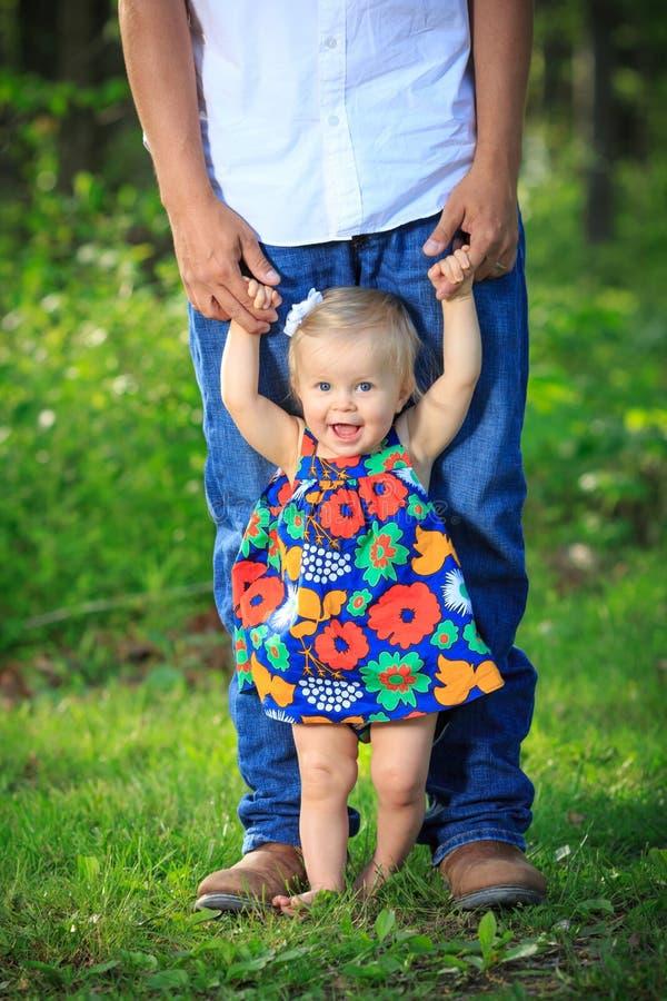 Ragazza che impara camminare con il papà fotografie stock