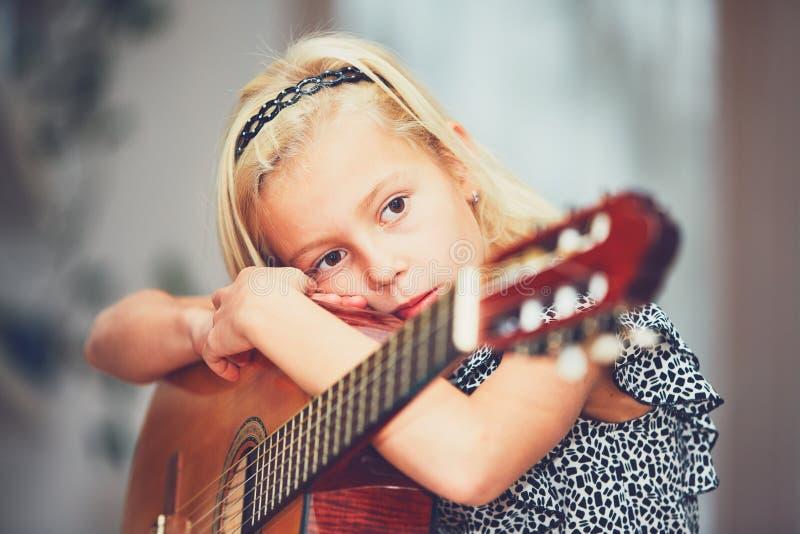 Ragazza che impara giocare alla chitarra immagine stock
