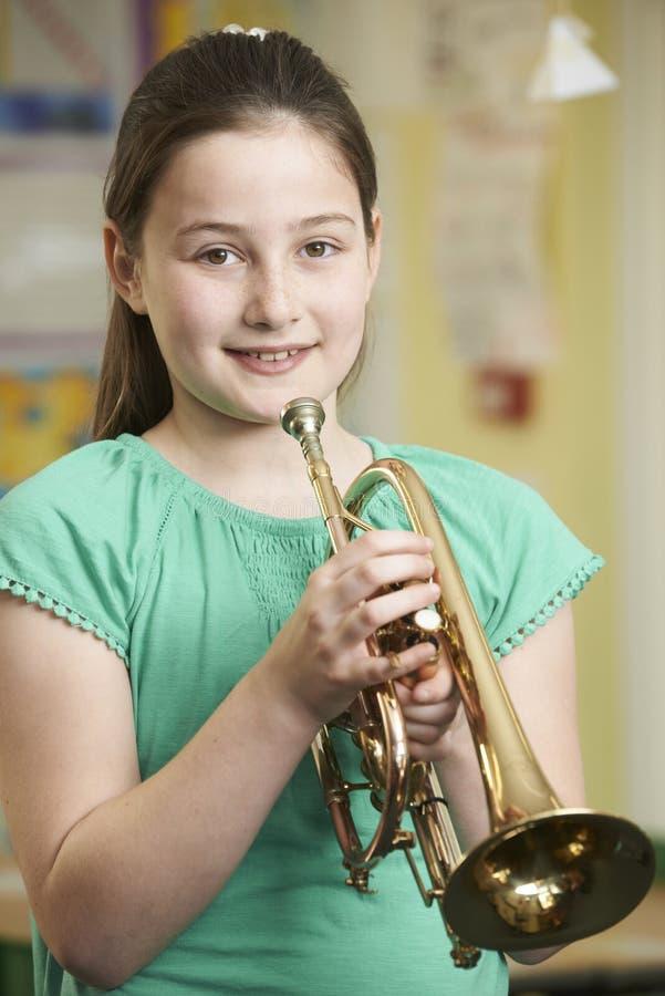 Ragazza che impara giocare tromba nella lezione di musica della scuola immagini stock