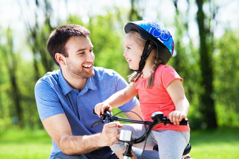 Ragazza che impara guidare una bici con suo padre fotografie stock libere da diritti