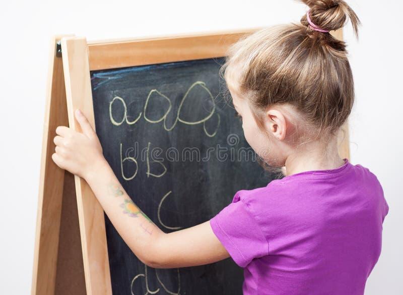 Ragazza che impara scrivere le lettere sulla lavagna fotografie stock libere da diritti