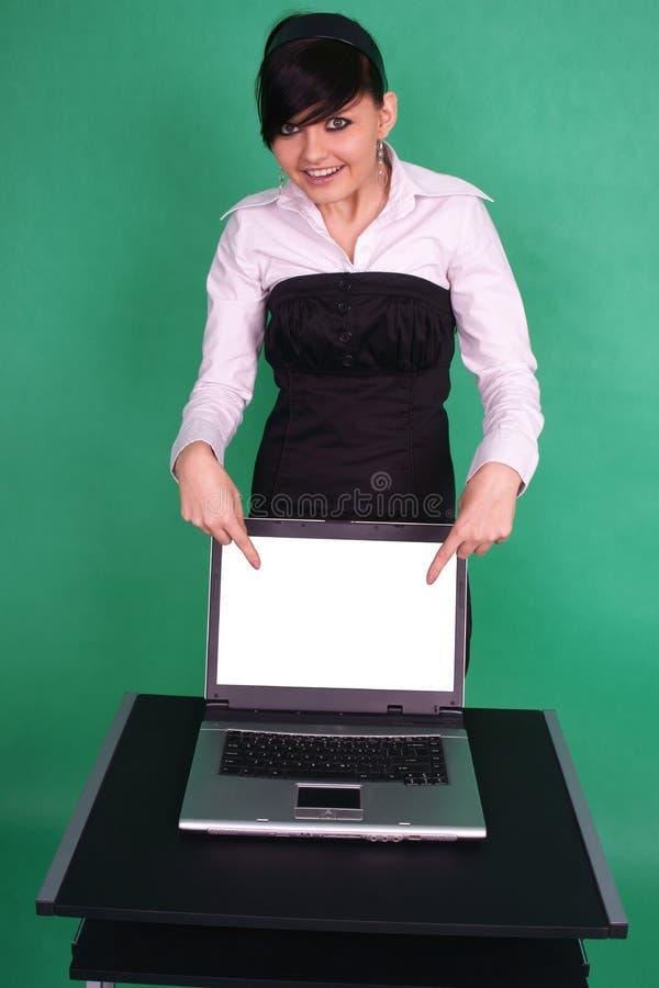 Ragazza che indica allo schermo in bianco del computer portatile. fotografie stock