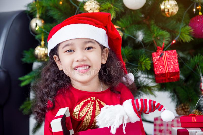 Ragazza che indossa il cappello ed i sorrisi di Santa mentre aprendo il regalo di natale a casa fotografie stock