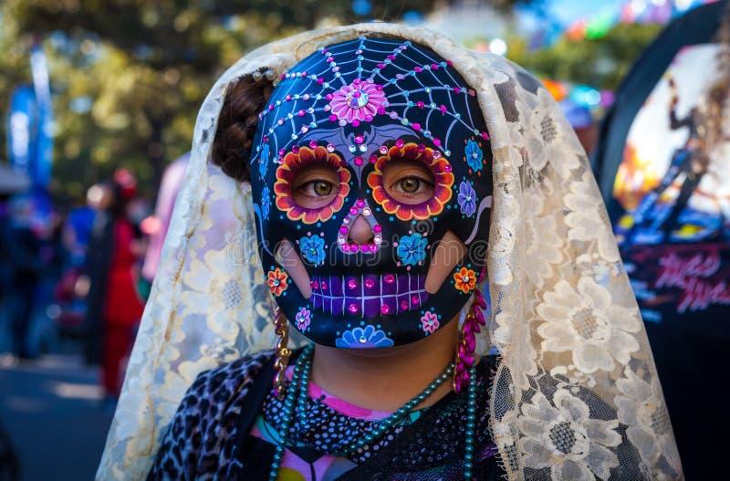 Ragazza che indossa la maschera variopinta del cranio dello zucchero e velo del pizzo per il diametro de immagine stock