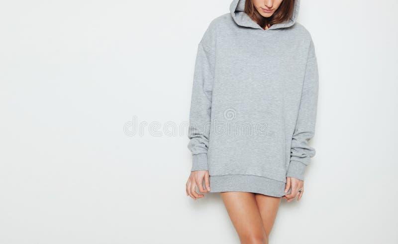 Ragazza che indossa maglia con cappuccio lunga in bianco e di grande misura Priorità bassa bianca fotografia stock libera da diritti