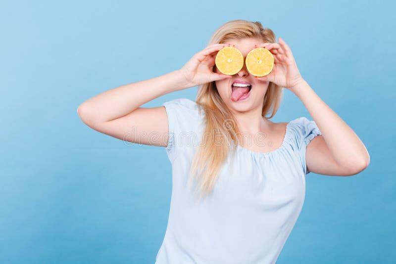Ragazza che la copre occhi di agrumi del limone fotografia stock