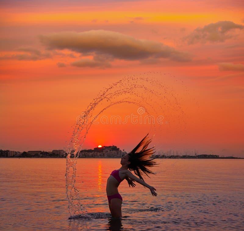 Ragazza che lancia vibrazione dei capelli alla spiaggia di tramonto immagini stock