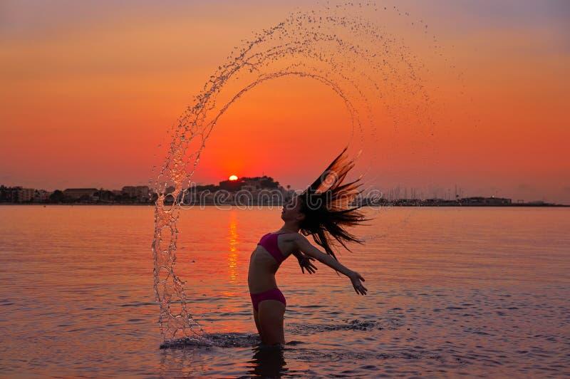 Ragazza che lancia vibrazione dei capelli alla spiaggia di tramonto immagini stock libere da diritti