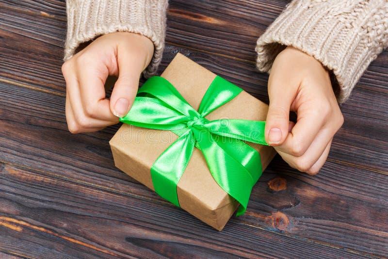 Ragazza che lega un arco verde semplice su un contenitore di regalo Avvolto nella carta normale del mestiere ed in nastro blu Toc fotografia stock libera da diritti