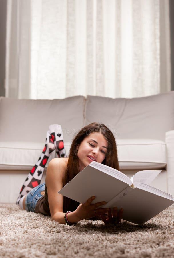 Ragazza che legge un grande libro sul suo salone immagini stock