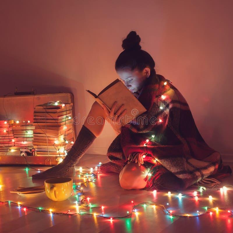 Ragazza che legge un libro sotto la coperta a casa fotografie stock libere da diritti