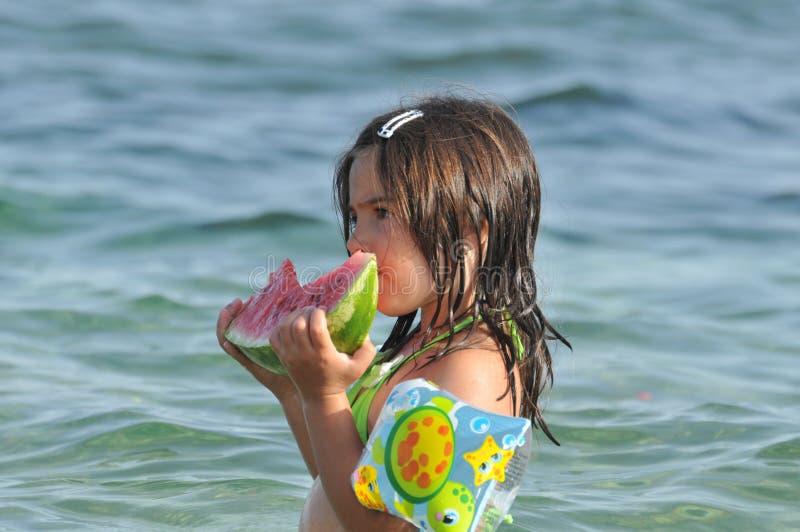 Ragazza che mangia anguria sulla spiaggia fotografia stock