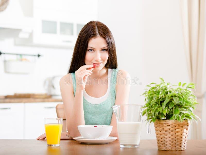 Ragazza che mangia fragola con il succo dell'agrume e del latte fotografia stock