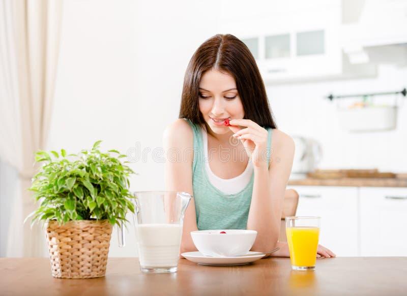 Ragazza che mangia fragola con latte e succo d'arancia fotografia stock libera da diritti