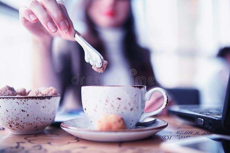 Ragazza che mangia i dolci di caffè fotografia stock