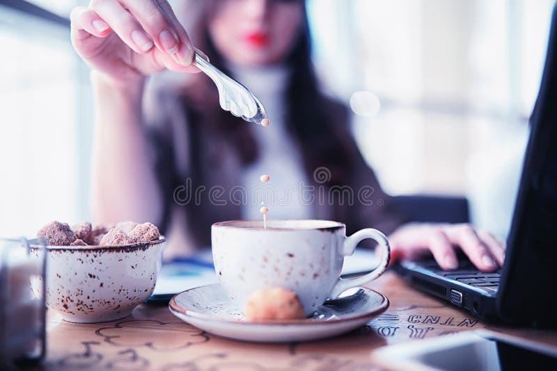 Ragazza che mangia i dolci di caffè immagini stock libere da diritti