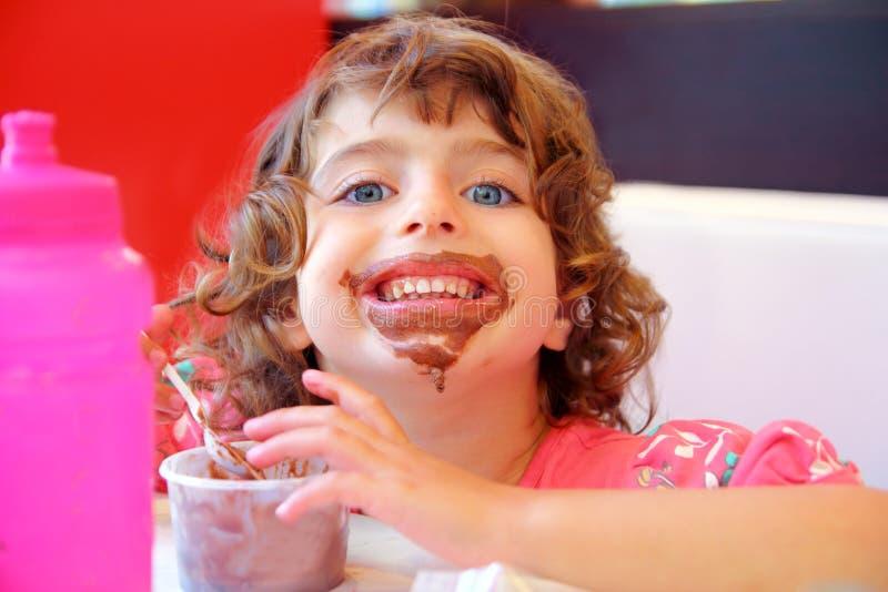 Ragazza che mangia il fronte sporco del gelato del cioccolato fotografia stock