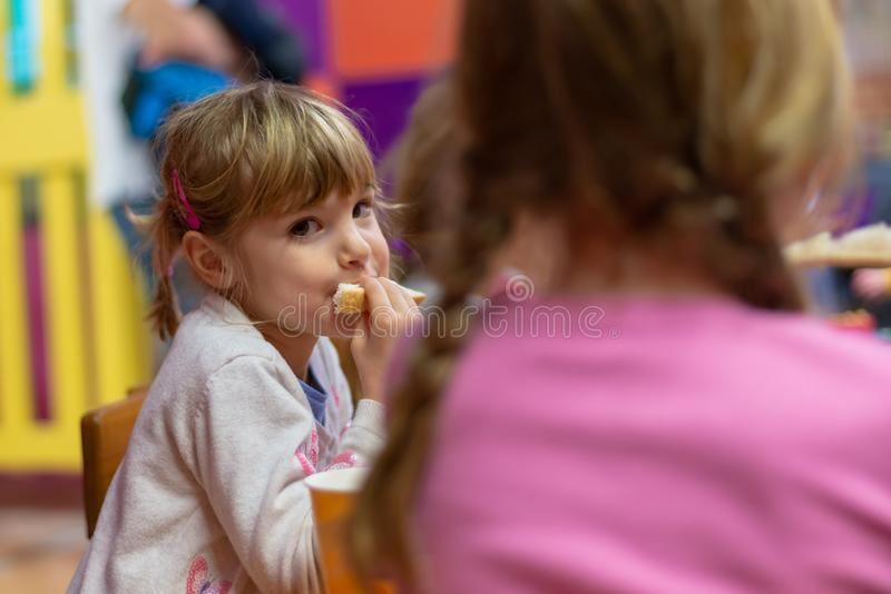 Ragazza che mangia panino alla festa di compleanno fotografia stock