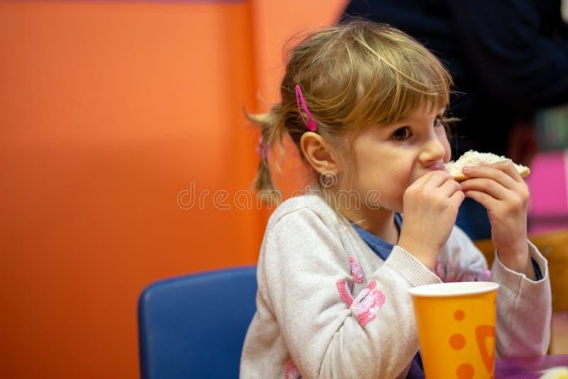 Ragazza che mangia panino alla festa di compleanno fotografie stock