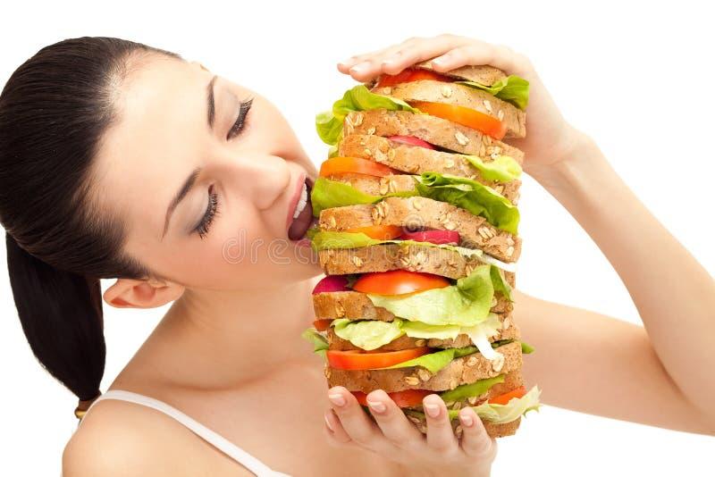 Ragazza che mangia panino, grande morso immagine stock