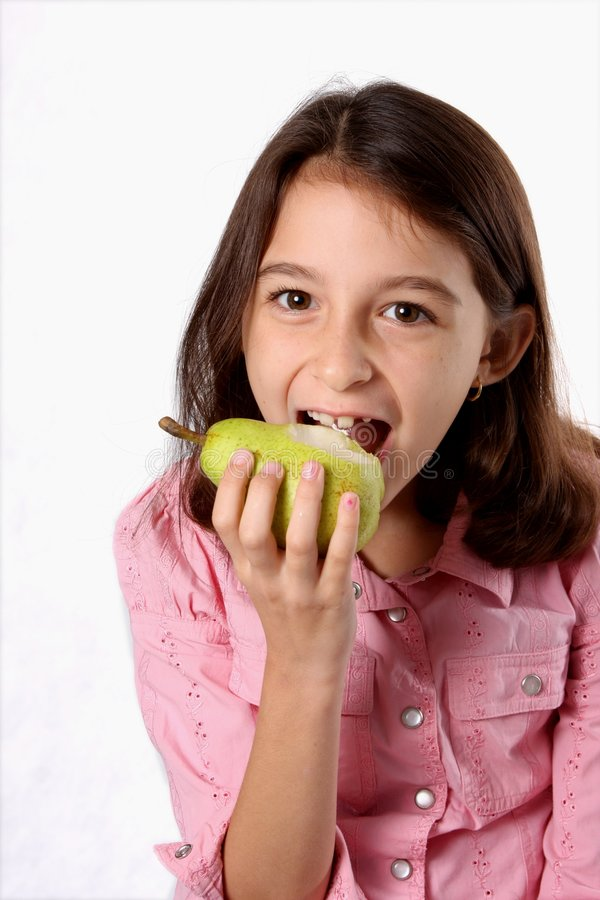 Ragazza che mangia pera verde fresca immagine stock