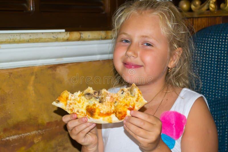 Ragazza che mangia pizza immagine stock