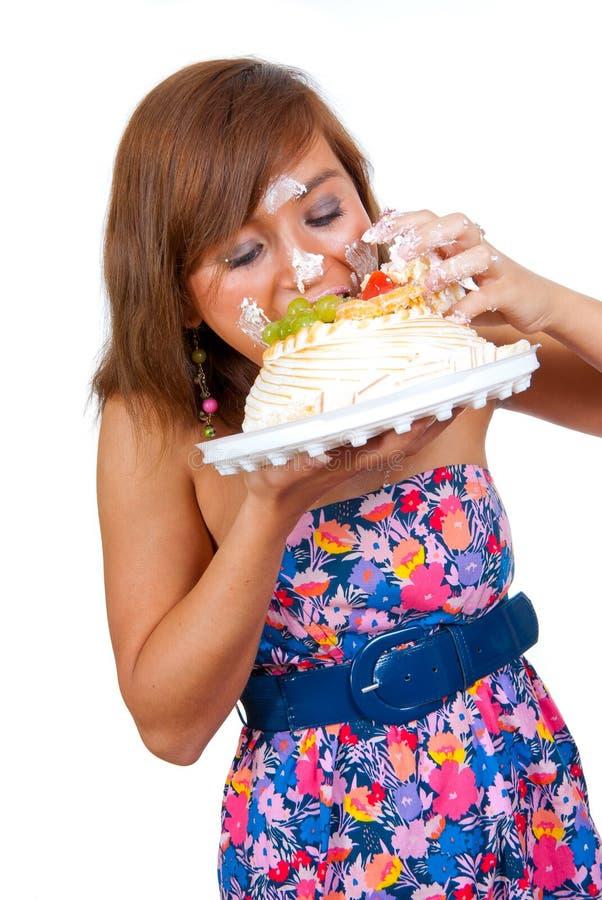 Ragazza che mangia torta con le sue mani fotografia stock
